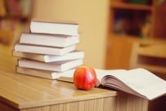 Libri e mela sul fondo vago delle biblioteche Fotografie Stock