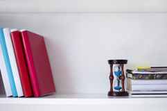 Libri e sandglass sullo scaffale bianco Fotografia Stock Libera da Diritti