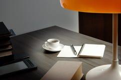 Libri e tazza di caffè su uno scrittorio di scrittura, acceso da una lettura-lampada fotografia stock libera da diritti