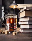 Libri e un vetro di tè con i pezzi di zucchero sulla tavola Fotografie Stock