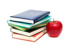 Libri e una mela rossa su una priorità bassa bianca Fotografie Stock Libere da Diritti