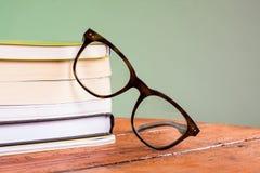 Libri e vetri su una tavola di legno Immagine Stock