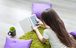 Libri elettronici della lettura Libro elettronico della lettura della bambina mentre trovandosi sul pavimento Immagini Stock
