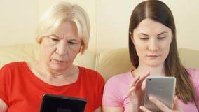 Libri elettronici moderni della lettura della figlia e della madre Concetto di divisione della lettura con i vostri bambini video d archivio