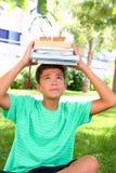 Libri impilati testa della holding dell'allievo dell'adolescente del ragazzo Immagine Stock Libera da Diritti