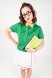 Libri nerd della tenuta della ragazza che esaminano macchina fotografica fotografia stock