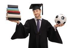 Libri non decisivi della tenuta del dottorando e un calcio Fotografia Stock
