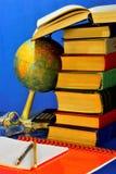 Libri, quaderni e un globo per la scuola Rifornimento-globo educativo per geografia, taccuino per le annotazioni, matita e penna immagini stock libere da diritti