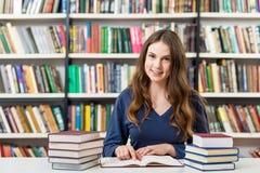 Libri reding della ragazza nella biblioteca, studiante Fotografia Stock