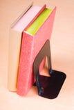 Libri rossi e dorati che si appoggiano sul reggilibro Immagine Stock