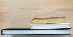 Libri sdriciti che stanno su uno scrittorio di legno con lo spazio della copia Immagini Stock