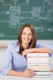Libri sorridenti di With Stack Of dell'insegnante allo scrittorio dell'aula Immagine Stock Libera da Diritti
