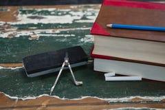 Libri, spolveratore e bussola sulla tavola di legno Fotografia Stock