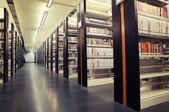 Libri sugli scaffali in biblioteca, scaffali per libri delle biblioteche con i libri, scaffali delle biblioteche, bookracks Fotografia Stock