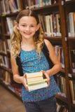 Libri svegli della tenuta della bambina in biblioteca Immagine Stock