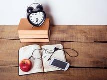 Libri, sveglia, blocco note, cellulare con le cuffie e mela su fondo di legno Fotografia Stock Libera da Diritti