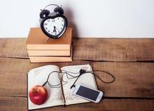Libri, sveglia, blocco note, cellulare con le cuffie e mela su fondo di legno Fotografie Stock Libere da Diritti