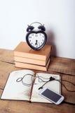 Libri, sveglia, blocco note, cellulare con le cuffie su fondo di legno Immagini Stock Libere da Diritti