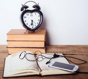 Libri, sveglia, blocco note, cellulare con le cuffie su fondo di legno Fotografia Stock Libera da Diritti