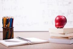 Libri, taccuino e matite sulla tavola con un bordo bianco vago Fotografia Stock Libera da Diritti