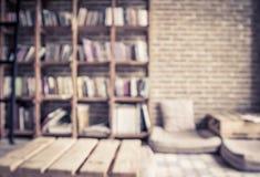 Libri vaghi sullo scaffale con il muro di mattoni in biblioteca pubblica Immagini Stock