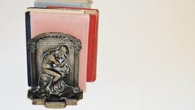 Libri Vecchi libri con il fermalibro del pensatore Immagini Stock Libere da Diritti