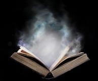 Libro abierto antiguo en el humo mágico Imagenes de archivo