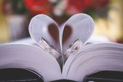 Libro abierto con los anillos de bodas Fotos de archivo libres de regalías