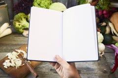 Libro abierto de la receta con las verduras en fondo de madera Visión superior foto de archivo