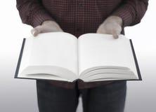 Libro abierto de la tenencia del hombre aislado en blanco Fotografía de archivo libre de regalías