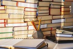 Libro abierto, libro de texto, ordenador portátil, lápices en biblioteca, pilas de archivo del texto de la literatura, estantes d fotos de archivo libres de regalías