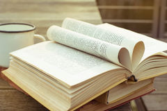 Libro abierto del vintage en la tabla de madera con la taza pasada de moda de té La página bajo la forma de corazón Vista lateral Imágenes de archivo libres de regalías