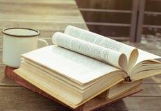 Libro abierto del vintage en la tabla de madera con la taza pasada de moda de té La página bajo la forma de corazón Vista lateral fotos de archivo
