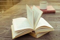 Libro abierto del vintage en la tabla de madera con la taza pasada de moda de té Vista lateral fotografía de archivo