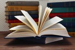 Libro abierto delante de la pila de libros Foto de archivo