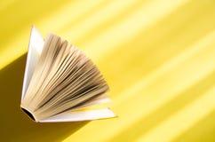 Libro abierto en un fondo amarillo en el sol brillante El concepto de educación, lectura, compra reserva Copie el espacio Fotografía de archivo libre de regalías
