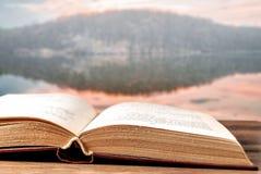 Libro abierto en una superficie y un paisaje de madera en el fondo imagen de archivo libre de regalías