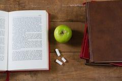 Libro abierto, manzana verde y tiza en la tabla de madera Fotos de archivo