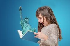 Libro abierto sorprendido de la tenencia de la niña con señora Liberty imagen de archivo