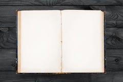 Libro abierto viejo con las páginas en blanco en la tabla de madera fotografía de archivo