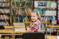 Libro adolescente del abarcamiento de la muchacha en la biblioteca Imagen de archivo