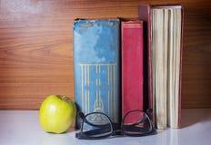 Libro antiguo con las lentes y la manzana verde Fotografía de archivo libre de regalías
