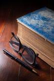 Libro antiguo con las lentes y la pluma Imagenes de archivo