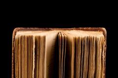 Libro antiguo tirado en fondo negro Imagenes de archivo