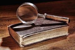Libro antiguo y lupa vieja Foto de archivo