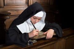 Libro antiguo y monja joven Foto de archivo libre de regalías