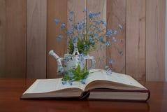 Libro aperto con i fiori di myosotis Immagini Stock