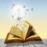 Libro aperto con la lampadina e le lettere Concetto di lettura Fotografia Stock