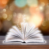 Libro aperto con la luce del bokeh sulle plance di legno Fotografia Stock