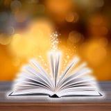 Libro aperto con la luce del bokeh sulle plance di legno Fotografie Stock Libere da Diritti